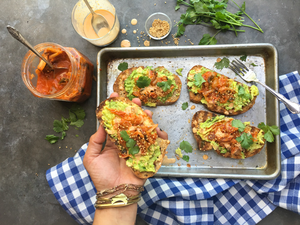 This isn't ordinary avocado toast. It's Avocado Kimchi Toast with a spicy tahini drizzle. Find recipe at Shutterbean.com